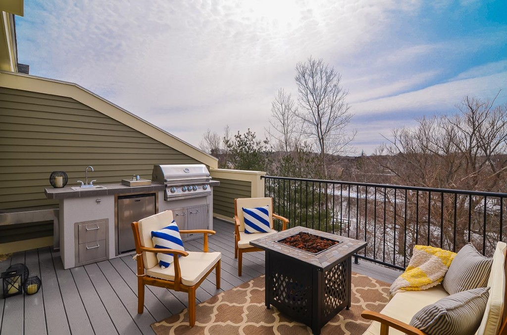 Awesome outdoor kitchen includes rotisserie grill, gas cooktop, sink, fridge, and storage doors / drawers